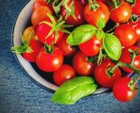 Les tomates-cerises fraîches dans un métal roulent sur une obscurité Photographie stock