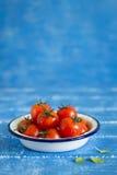 Les tomates-cerises fraîches dans un vintage ont émaillé le plat Photographie stock libre de droits