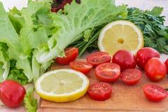 Les tomates-cerises, les plastiques de citron, le persil et les feuilles de laitue couvertes de gouttes de l'eau se trouvent sur  Photo libre de droits