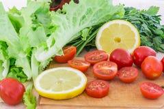 Les tomates-cerises, les plastiques de citron, le persil et les feuilles de laitue couvertes de gouttes de l'eau se trouvent sur  Images libres de droits