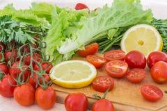 Les tomates-cerises, les plastiques de citron, le persil et les feuilles de laitue couvertes de gouttes de l'eau se trouvent sur  Photo stock