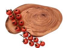 Les tomates-cerises se trouvent sur un panneau en bois d'huile de séchage, d'isolement sur le fond blanc Images stock