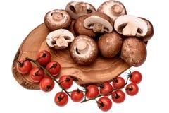 Les tomates-cerises se trouvent sur un panneau en bois d'huile de séchage, d'isolement sur le fond blanc Photos libres de droits