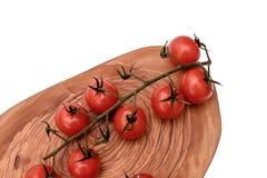 Les tomates-cerises se trouvent sur un panneau en bois d'huile de séchage, d'isolement sur le fond blanc Photographie stock