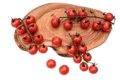 Les tomates-cerises se trouvent sur un panneau en bois d'huile de séchage, d'isolement sur le fond blanc Images libres de droits