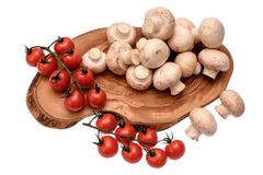 Les tomates-cerises se trouvent sur un panneau en bois d'huile de séchage, d'isolement sur le fond blanc Photo stock
