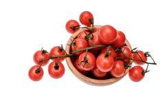 Les tomates-cerises se trouvent sur un panneau en bois d'huile de séchage, d'isolement sur le fond blanc Image stock