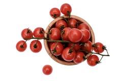 Les tomates-cerises se trouvent sur un panneau en bois d'huile de séchage, d'isolement sur le fond blanc Photographie stock libre de droits