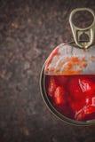 Les tomates coupées dans le métal peuvent dans la verticale en pierre de table Photographie stock