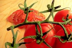 Les tomates coupées en tranches se situe à l'arrière-plan d'une brindille des tomates image stock
