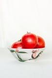Les tomates dans une cuvette couvre de tuiles le fond blanc Photo libre de droits