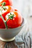 Les tomates dans une cuvette sur la vieille verticale en bois de table dégrossissent Images stock