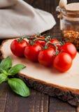 Les tomates fraîches avec le basilic et les épices cognent sur le conseil grunge Photographie stock libre de droits