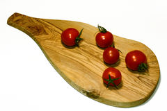 Les tomates fraîches d'isolement de cerise sur la planche en bois apprêtent photographie stock libre de droits