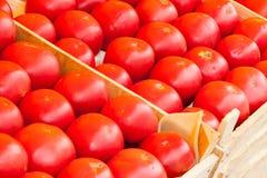 Les tomates juteuses rouges se trouvent sur un compteur de boutique Image stock