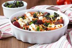 Les tomates ont fait cuire au four avec du feta de fromage, saucisses fumées, herbes, olives Photos libres de droits
