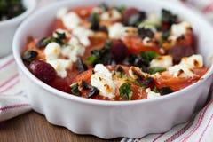Les tomates ont fait cuire au four avec du feta de fromage, saucisses fumées, herbes, olives Images libres de droits