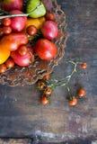 Les tomates oranges de tomates de tomates de tomates rouges colorées de jaune avec de l'eau se laisse tomber sur le fond concret  Images libres de droits