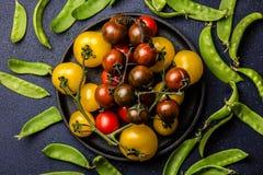 Les tomates rouges et jaunes sur la fonte noircissent le pâté et le pois sur le fond noir Vue supérieure Images libres de droits