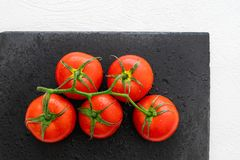 Les tomates rouges fraîches avec des gouttes de l'eau de ci-dessus, se ferment  image stock