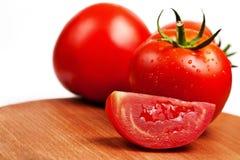 Les tomates rouges sur un panneau de découpage ont isolé Image stock