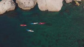 Les touristes aériens sur des kayaks naviguent sur la mer contre la côte rocheuse banque de vidéos