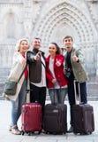 Les touristes adultes avec le bagage posent sur la rue Photographie stock libre de droits