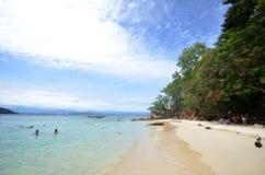 Les touristes apprécient la plage blanche de sable de l'île de Sapi dans Sabah images stock