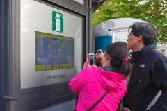 Les touristes asiatiques s'approchent de l'information interactive Image libre de droits