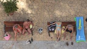 Les touristes détendent sur un banc en plage de Magaluf Image libre de droits