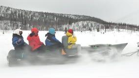 Les touristes dans des vestes colorées reposent et montent le bateau de banane de neige banque de vidéos