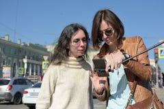 Les touristes de jeunes dames font des selfies à un pont dans le St Petersbourg, Russie, et ont l'amusement devant la caméra photographie stock libre de droits