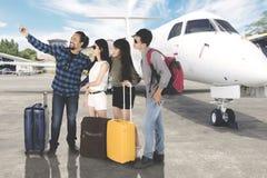 Les touristes divers prennent une photo près d'un avion Photo libre de droits
