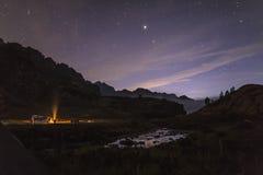 Les touristes et les chasseurs sont passionnés autour du feu de camp la nuit dans images libres de droits