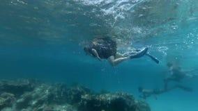 Les touristes et les plongeurs locaux nagent au-dessus du récif coralien banque de vidéos