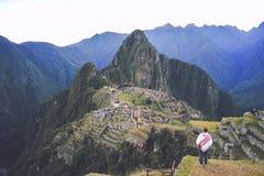 Les touristes féminins se tient sur le premier plan et regarde Machu Picchu, la ville perdue des Inca image stock