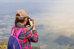 Les touristes féminins sur la montagne prennent le beau paysage images stock