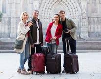 Les touristes heureux avec le bagage posent sur la rue Photo stock