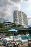 Les touristes les prennent un bain de soleil près d'une piscine dans l'hôtel d'A-ONE photos stock