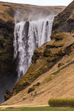 Les touristes marchent vers le haut de la voie à la cascade de Skogafoss Image libre de droits