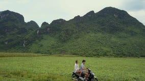 Les touristes montent le scooter sur des champs contre de vieilles montagnes supérieures banque de vidéos