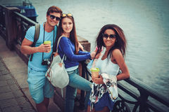 Les touristes multi-ethniques d'amis avec des tasses de carte et de café s'approchent de la rivière dans une ville Photographie stock libre de droits