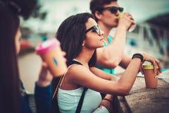 Les touristes multi-ethniques d'amis avec des tasses de carte et de café s'approchent de la rivière dans une ville Images stock