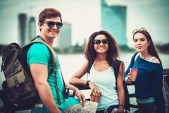 Les touristes multi-ethniques d'amis avec des tasses de carte et de café s'approchent de la rivière dans une ville Image stock
