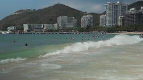 Les touristes nagent dans les vagues fortes de la mer de sud de la Chine sur la vidéo de longueur d'actions de plage de Dadonghai banque de vidéos