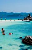 Les touristes naviguants au schnorchel détendent sur la plage Image stock