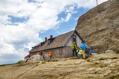 Les touristes non identifiés visitent l'abri de montagne en montagnes de Bucegi en Roumanie Photo stock