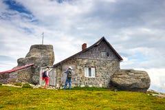 Les touristes non identifiés visitent l'abri de montagne en montagnes de Bucegi en Roumanie Photos libres de droits