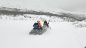 Les touristes ont plaisir à monter le bateau de banane de neige parmi des collines de neige banque de vidéos