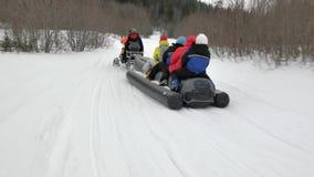 Les touristes ont plaisir à monter le long bateau de banane gris de neige avec le guide banque de vidéos
